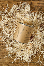 Load image into Gallery viewer, Image of the back of a tin of Disappointment with a kraft label showing the faux ingredients and side effects. Tin is sat in a nest of wood wool.