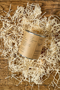 Image of the back of a tin of Disappointment with a kraft label showing the faux ingredients and side effects. Tin is sat in a nest of wood wool.