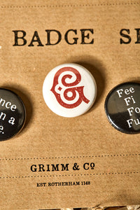 Image of a white button badge with the Grimm & Co red 'G' monogram on the front