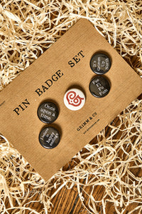 Image of set of 5 button badges on a kraft card backing. Slogans incclude Once upon a time, I believe in happy endings, Fee Fi Fo Fum, It's Grimm Up North and the red Grimm & Co 'G' monogram