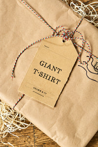 Image shows Giant T-Shirt packaged in kraft brown paper and tied with bakers twine with kraft paper label. Packaged shown ready for delivery