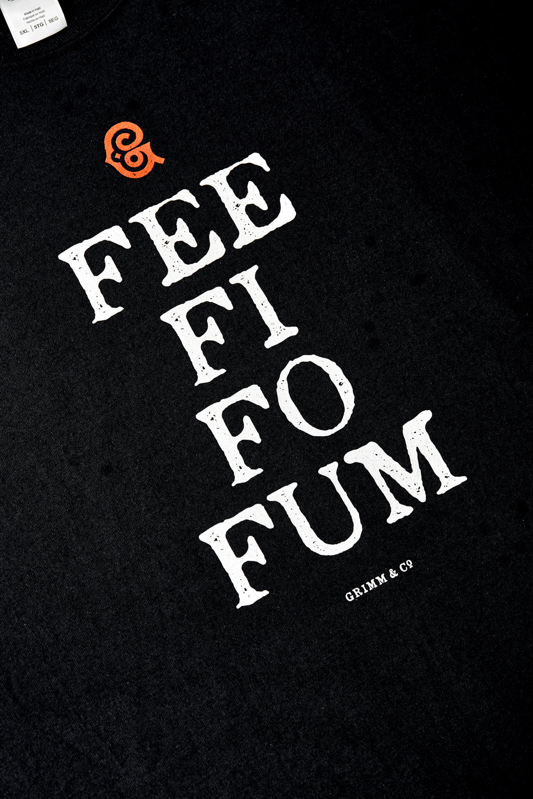 Image shows black cotton t-shirt printed with white text saying 'FEE FI FO FUM' with a red Grimm & Co 'G' monogram at the top