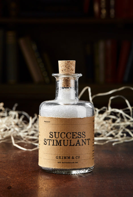 Image shows a bottle of Success Stimulant, otherwise known as white, scented bath salts in a glass bottle with cork lid and a kraft paper label