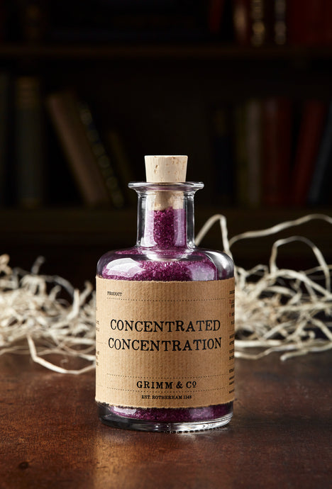 Image of Concentrated Concentration, otherwise known as scented, purple bath salts in a glass bottle with cork