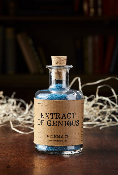 Image of Extract of Genius, otherwise known as scented, blue bath salts in a glass bottle with cork. On this label the spelling of the word Genius is deliberately misspelled to 'Genious' with the 'o' crossed out