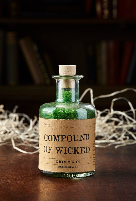 Image of Compound of Wicked, otherwise known as scented, green bath salts in a glass bottle with cork