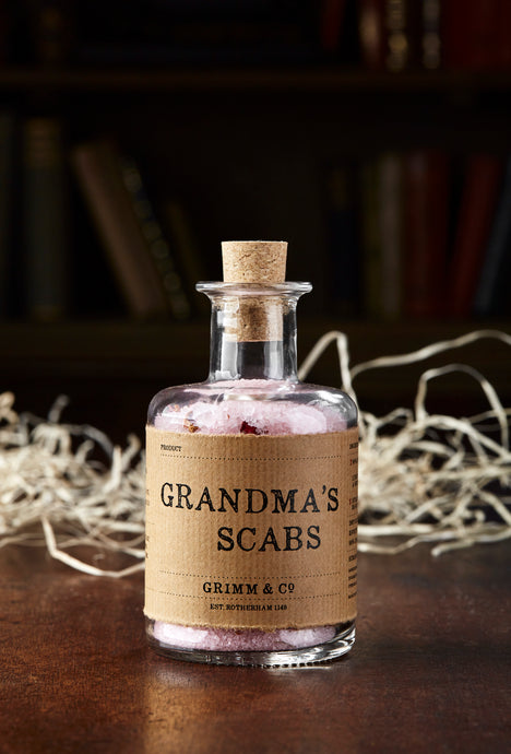 Image shows a bottle of Grandma's Scabs potion, a blass bottle with cork containing pale pink bath salts and dried rose petals. Bottle is wrapped with a kraft paper label.