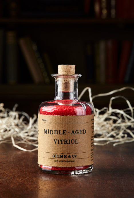 Image shows a bottle of Middle Aged Vitriol, otherwise known as red, scented bath salts in a glass bottle with cork lid and a kraft paper label
