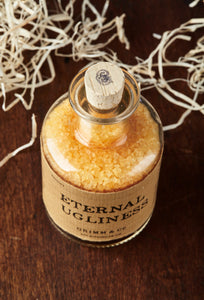 Top view image of Eternal Ugliness otherwise known as scented, orange coloured bath salts in a glass bottle with cork