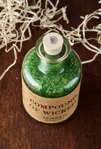 Top view image of Compound of Wicked otherwise known as scented, green bath salts in a glass bottle with cork