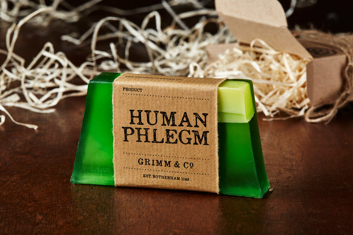 Image of Human Phlegm bar, a green and white melon scented soap slice shown with a kraft paper label.
