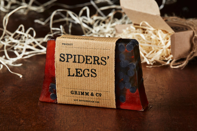 Image of a Spiders Legs bar, a brown and black cedarwood, grapefruit, and amber scented soap slice shown with a kraft paper label.