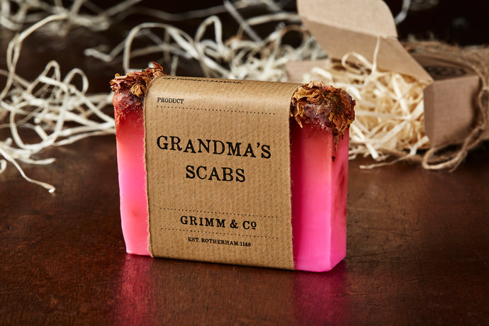 Image of Grandma's Scabs bar, otherwise known as a pink rose scented soap slice topped with dried rose petals, shown with kraft paper label