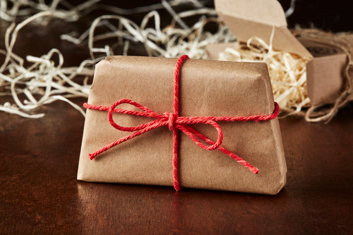 Image of wrapped soap slice in kraft paper tied with red twine. Item shown as it would arrive once ordered.