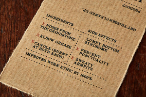 Image shows kraft paper label for Human Blood, Sweat and Tears bar, a pomegranate scented soap slice. Label lists the faux ingredients and side effects.