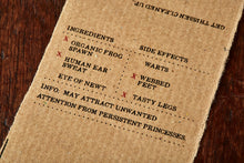 Load image into Gallery viewer, Image shows kraft paper label for Frog Spawn bar, a kiwi scented soap slice. Label lists the faux ingredients and side effects.