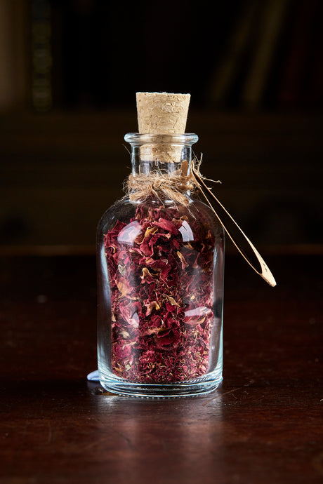 Image of Happily Ever After, a small decorative glass bottle with cork containing dried rose petals and tied with twine and a kraft paper label