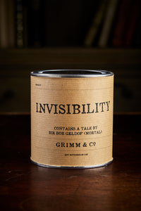 Image of a tin of Invisibility. A silver tin wrapped in a kraft paper label