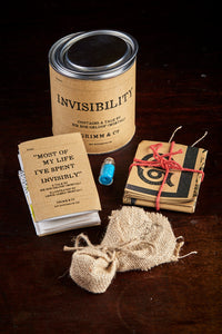 A detail image of a tin of Invisibility showing contents including a folded up illustrated story written by Sir Bob Geldof, a hessian wrapped pouch containing glow in the dark pebbles, a tiny jar of glitter and a folded up illustrated map of Rotherham town centre