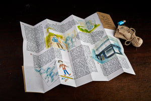 A detail image of the unfolded illustrated story written by Sir Bob Geldof and illustrated by Lewis James. Next to story is the hessian pouch of glow in the dark pebbles and tiny jar of glitter.