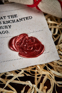 Close up detail image of the red wax seal on the certificate of authenticity, stamped with the Grimm & Co 'G' monogram