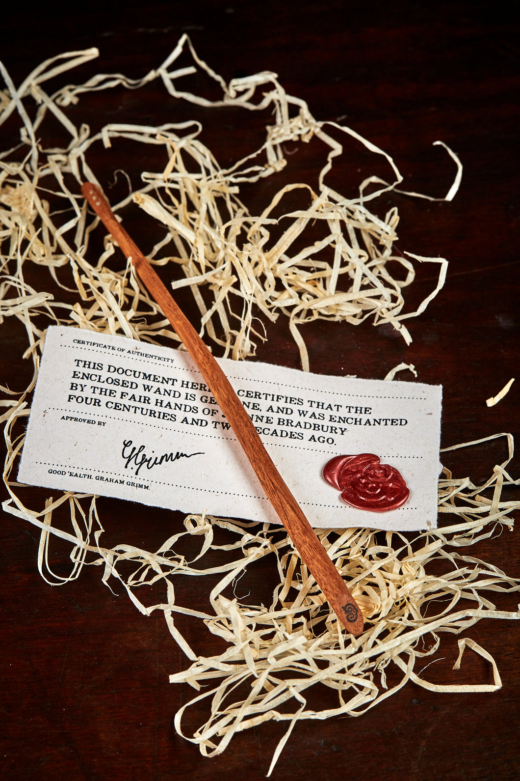 Image of a large handmade advanced wand, wooden decorative wand stamped with a black Grimm & Co 'G' monogram at the base of the handle. Wand has three dots of sterling silver at the tip, wand wood is a rich brown colour and comes with a wax sealed certificate of authenticity