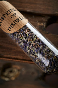 Close up detailed image of Suspension of Disbelief contents, otherwise known as a glass boiling tube with orange rubber bung, containing dried lavender flowers