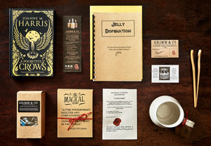 Image shows the contents of a Novel Tea Box laid out flat. The set shows the novel A Pocketful of Crows by Joanne Harris, a bookmark, a copy of Jelly Domination by Carr Junior School,  a Grimm and Co business card, a Snail Pottery business card, a set of bamboo tea tongs, a ceramic mug, an unscrolled certificate of awesome, some printed quote cards on kraft card,  and a box of english breakfast tea.