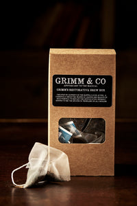 Image of Grimm's Restorative Brew Box, a kraft box with black labelling containing 15 english breakfast silk tea temples, with one teabag laid out next to box