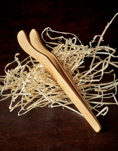 Image shows a set of light bamboo tea tongs resting on wood wool.
