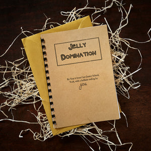 Image shows a copy of Jelly Domination written by pupils from Carr Junior School, with a golden envelope underneath, which it will be presented inside within the Novel Tea Box.