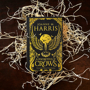 Image of the front cover of the hardback book A Pocketful of Crows written by Joanne Harris, resting on a pile of wood wool.