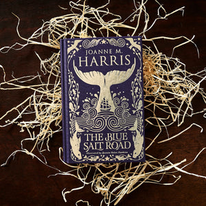 Image of the front cover of the hardback book The Blue Salt Road written by Joanne Harris, resting on a pile of wood wool.