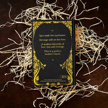 Load image into Gallery viewer, Image of the back cover of the hardback book A Pocketful of Crows written by Joanne Harris, resting on a pile of wood wool.