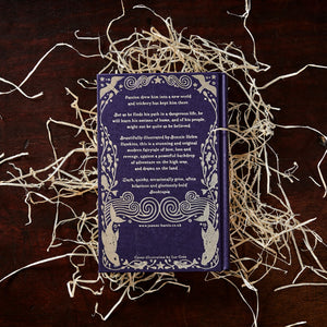 Image of the back cover of the hardback book The Blue Salt Road written by Joanne Harris, resting on a pile of wood wool.
