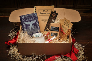 Image shows an open Novel Tea Box. A gift box bundle featuring a choice out of three novels written by Joanne Harris. The book in this image is The Blue Salt Road. The set shows a box of english breakfast tea, a copy of Jelly Domination written by pupils from Carr Junior School, a Grimm and Co. bookmark, a ceramic mug, a set of bamboo tea tongs, some printed quote cards on kraft card and a scrolled certificate of awesome tucked within wood wool. The box is surrounded by wood wool and red ribbon.