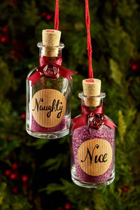 Detail image of festive greetings card one of 4 designs, this design shows a photograph of twin mini potion bottles labelled 'Naughty' and 'Nice' where the 'Nice' bottle is filled with bath salts and 'Naughty' has barely any salts inside