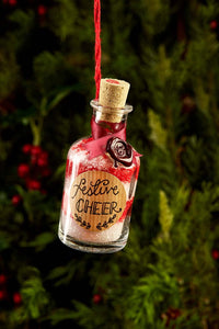 Detail image of festive greetings card one of 4 designs, this design shows a photograph of a mini potion bottle filled with alternative red and white layers of bath salts, labelled 'Festive Cheer'
