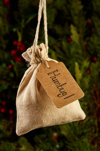 Detail image of festive greetings card one of 4 designs, this design shows a photograph of a linen drawstring pouch with a kraft tag labelled 'Humbug!'