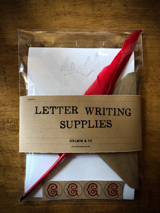 Image shows the pack of Letter Writing Supplies containing 8 sheets of cream textured paper printed with a design of potion bottles and wording, a red biro quill, 4 kraft envelops embossed with the Grimm & Co 'G' monogram and set of 4 red monogram stickers