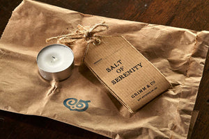 Image shows a tealight and Salt of Serenity kraft label, resting on the brown paper bag it is delivered in.