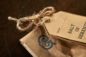 Closeup image of the Salt of Serenity label tied to the top of the brown paper tealight bag.