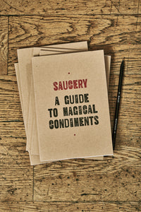 Image shows a few kraft card notebooks in a pile with the top one displaying the slogan 'SAUCERY: A GUIDE TO MAGICAL CONDIMENTS'. Notebooks are shown with a Word Wand pencil.