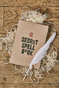 Image shows a kraft notebook displaying the slogan ''SECRET SPELL BOOK'. Notebook is shown with a white biro quill.