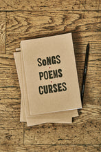 Load image into Gallery viewer, Image shows a few kraft card notebooks in a pile with the top one displaying the slogan 'SONGS, POEMS, CURSES'. Notebooks are shown with a Word Wand pencil.