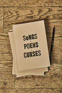 Image shows a few kraft card notebooks in a pile with the top one displaying the slogan 'SONGS, POEMS, CURSES'. Notebooks are shown with a Word Wand pencil.