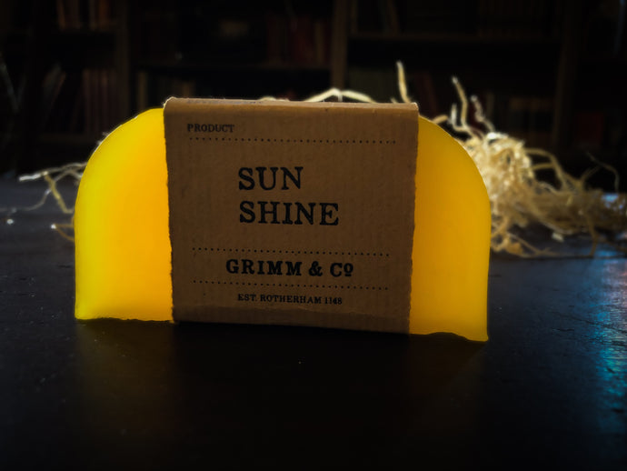Image of a Sun Shine bar, a bright yellow solid shampoo slice with a kraft paper label