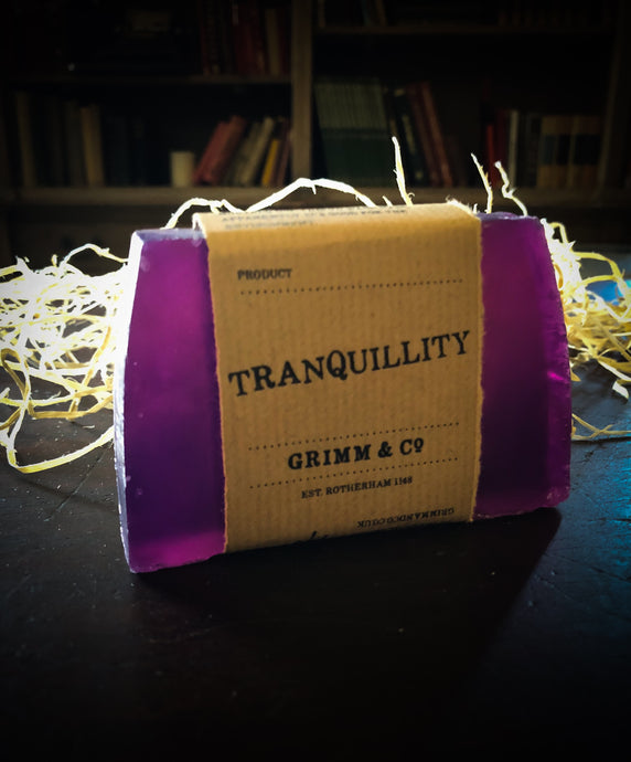 Image of a Tranquility bar, a purple solid shampoo slice with a kraft paper label