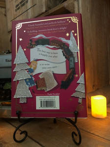 mage of the back of the hardback book Pages & Co: Tilly and the Map of Stories written by Anna James and illustrated by Paola Escobar. Displayed on a book stand with candles.
