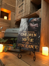 Load image into Gallery viewer, Image of front cover of paperback book Children of Vengeance and Virtue stood in book stand with a candle